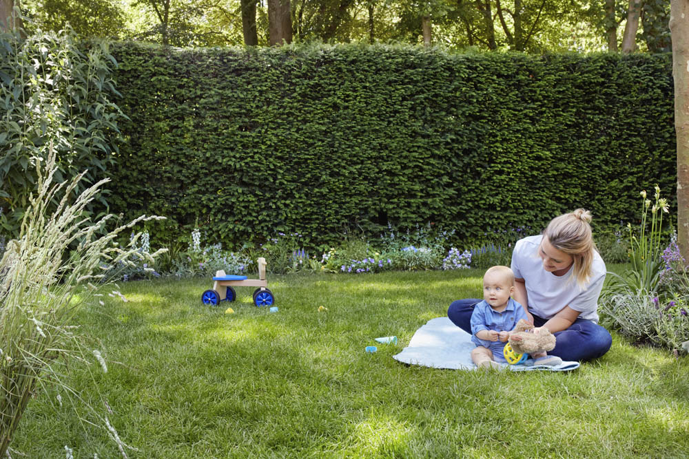 Bébé et sa maman assis sur l'herbe