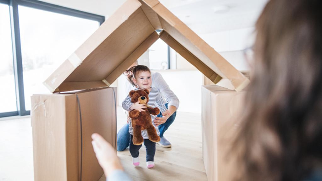 Enfant qui joue dans une cabane en carton dans la maison
