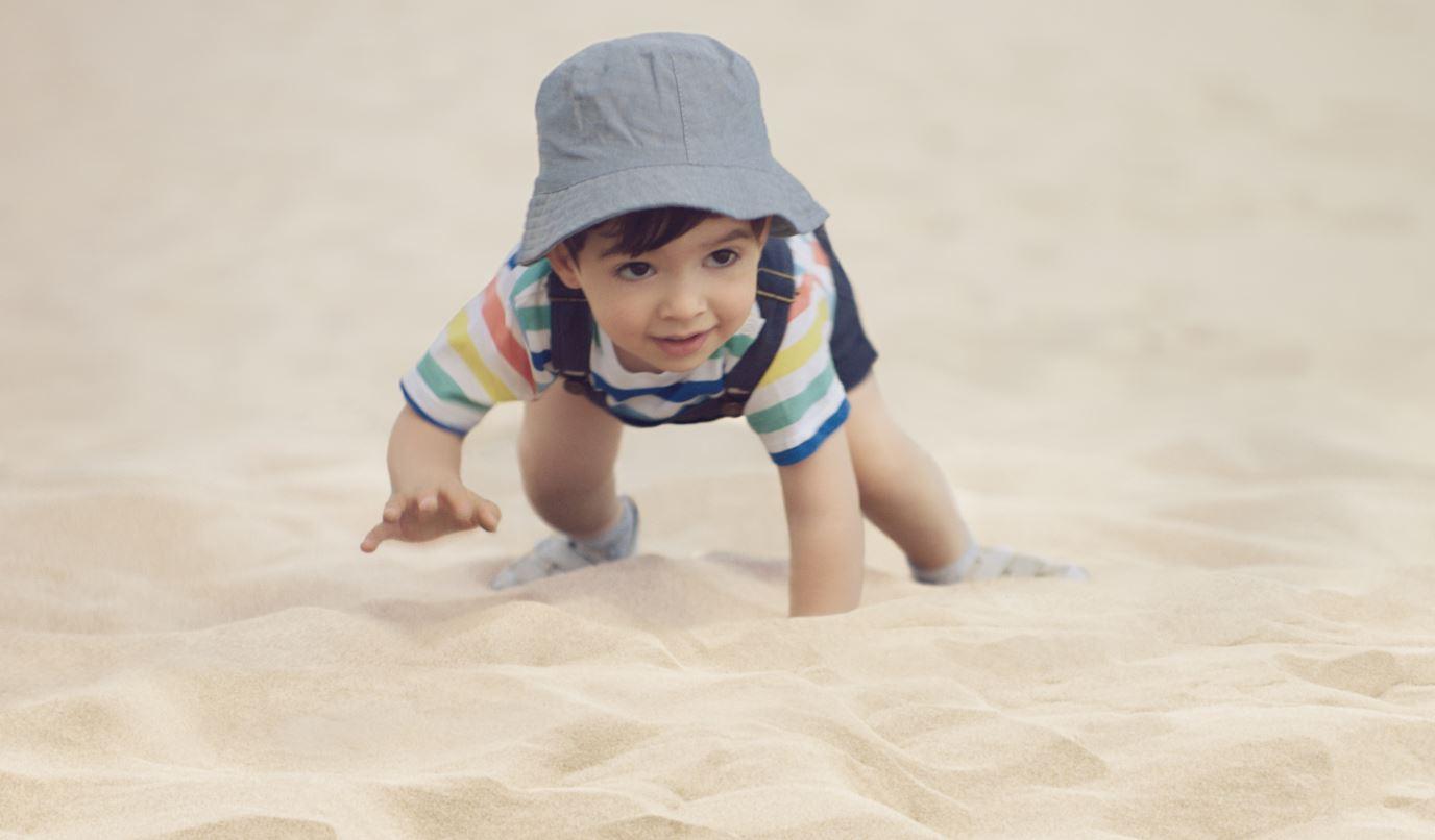 Bébé rampe dans le sable